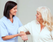 nurse giving support to senior woman