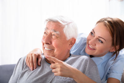 close-up of a happy female nurse pointing at something to senior man