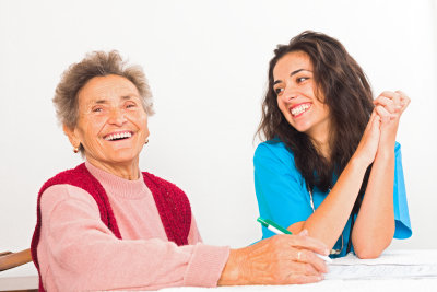 Happy elderly women with kind social services provider nurse laughing