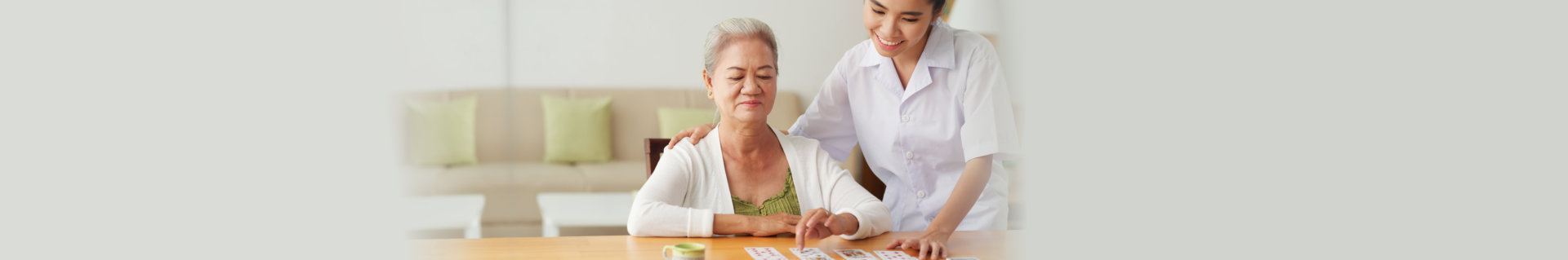 caregiver and senior woman playing cards