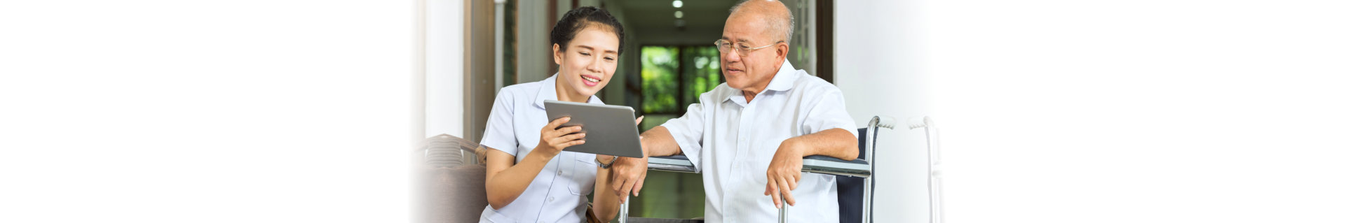 caregiver showing the tablet to the senior man