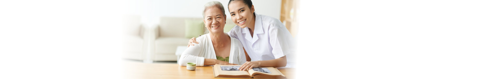 caregiver and senior woman reading a book